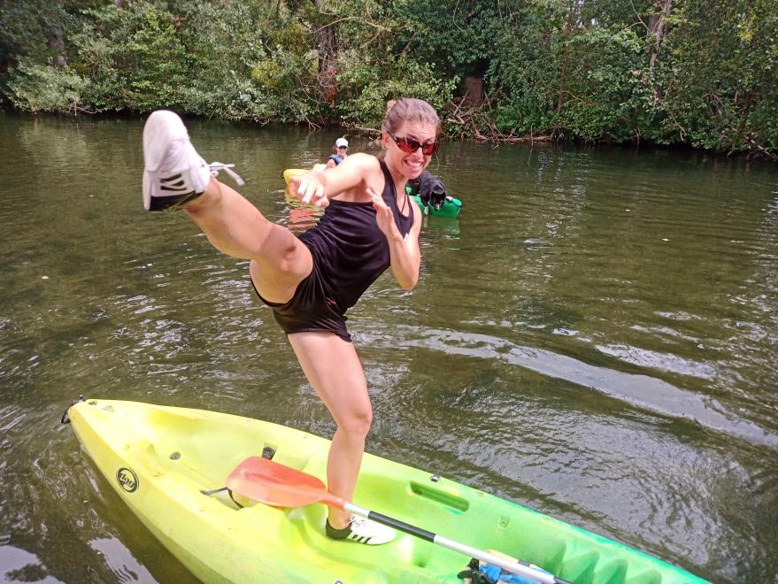 Corinne faisant un coup de pied circulaire en équilibre sur un kayak